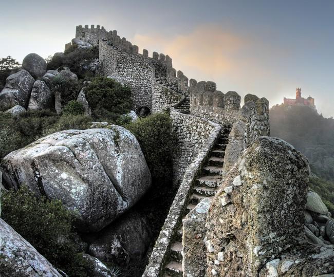 Sintra, Portogallo, Castelo dos Mouros. Sintra è per il Portogallo una meta turistica. Di quelle vere, con turisti veri muniti di macchina fotografica, smartphone e bastoni per i selfie. Si tratta di un luogo intriso di una magia tutta sua e per questo motivo va visitato.