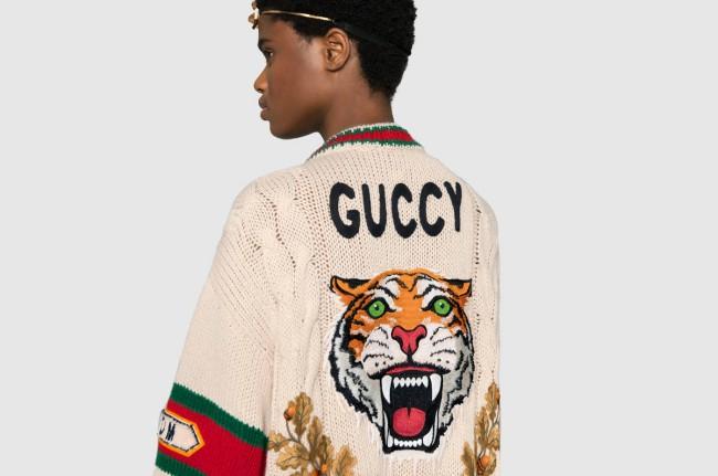 """Gucci, light cardigan in lana a coste ricamato con logo """"Guccy"""". La logomania e la tendenza alla caricatura: vediamo il caso DEISEL a Canal Street, New York e altre celebri caricature e falsi del mondo della moda!"""