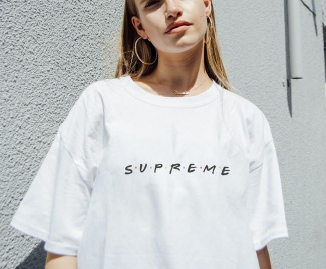 """T-shirt bianca di Fornever con logo """"Supreme"""" in stile serie TV Friends. La logomania e la tendenza alla caricatura: vediamo il caso DEISEL a Canal Street, New York e altre celebri caricature e falsi del mondo della moda!"""